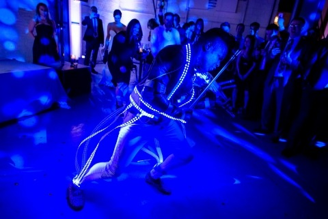 DJ Timothee Lovelock plays electric violin while wearing an LED lighted suit during a wedding at Moonlight Studios in Chicago.