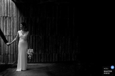 Gipuzkoa wedding photographer captured this black and white portrait of a bride holding hands with the groom in front of a wooden wall