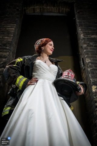 Minneapolis wedding photographer captured this portrait of a bride proudly holding her fire fighter helmet while wearing her fire coat over her wedding dress