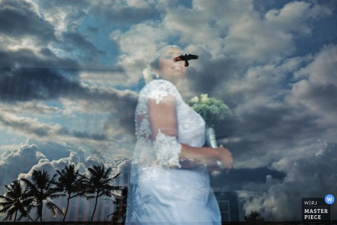 Sri Lanka wedding photographer captured the reflection of palm trees, clouds, and a soaring hawk as the bride stands on the other side of the glass