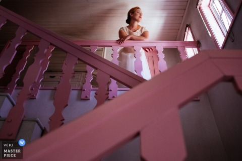 Porto wedding photographer captured this image looking up at a bride as she leans on a pink banister while looking out a window