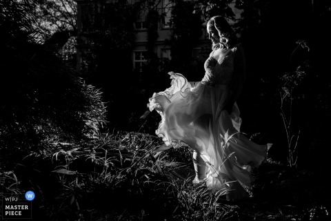 Rotterdam wedding photographer captured this black and white portrait of a bride in a grassy yard while her filmy dress is blown by the wind