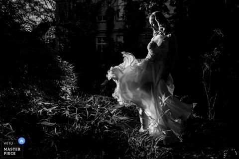 La photographe de mariage de Rotterdam a capturé ce portrait en noir et blanc d'une mariée dans un jardin herbeux, tandis que sa robe filmée est balayée par le vent
