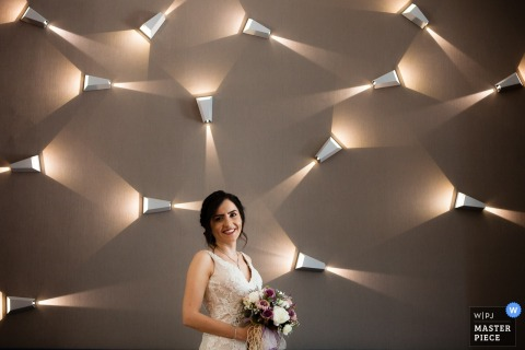 Istanbul wedding photographer captured this smiling brides portrait as she stands in front of a wall covered in lights
