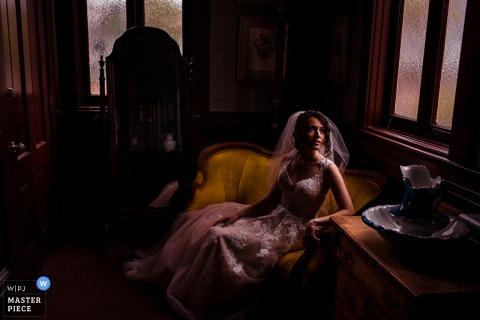 圣地亚哥婚礼摄影师拍摄了这张新娘坐在芥末黄色沙发上,盯着窗外望去的肖像