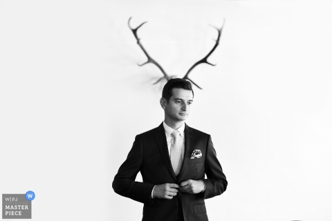 Bucharest wedding photographer gives a new meaning to stag as the groom poses in front of antlers hanging from the wall
