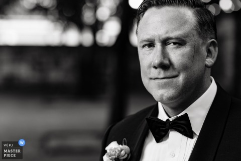 This black and white portrait of the groom smiling at the camera was captured by an Austin wedding photographer