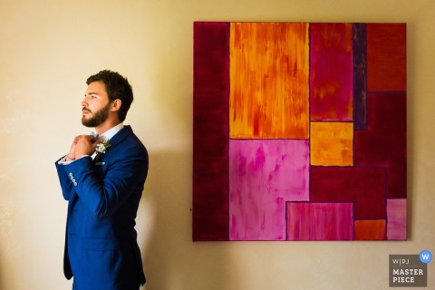 Miami wedding photographer captured this photo of a groom straightening his bow tie next to an abstract painting