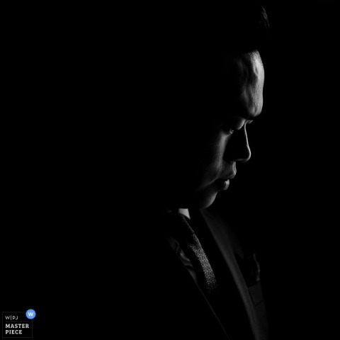 重慶婚禮攝影師拍攝了這張黑白新郎的肖像,同時他在遠處莊嚴地盯著