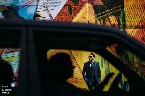 Der deutsche Hochzeitsfotograf hat dieses Porträt des Bräutigams durch das Fenster eines vorbeifahrenden Autos aufgenommen, als er vor einem großen Wandgemälde steht