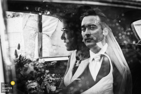 De huwelijksfotograaf in Frankrijk gebruikt op creatieve wijze reflecties, omdat we de bruidegomsafbeelding zien die op het autoraam is aangebracht waar de bruid in zit