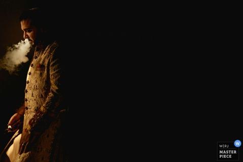 Der Londoner Hochzeitsfotograf hat dieses Bild des Bräutigams aufgenommen, der in seiner Hochzeitskleidung vor einem völlig dunklen Hintergrund raucht