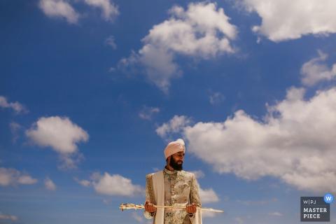 Dieses Porträt des Bräutigams, der vor einem strahlend blauen Himmel voller flauschiger weißer Wolken steht, wurde von einem Londoner Hochzeitsfotografen aufgenommen