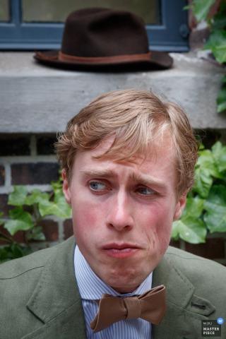 Der Amsterdamer Hochzeitsfotograf hat dieses Porträt des Bräutigams aufgenommen, als er mit einem ratlosen Gesichtsausdruck sitzt und sein Hut auf der Fensterbank hinter ihm ruht