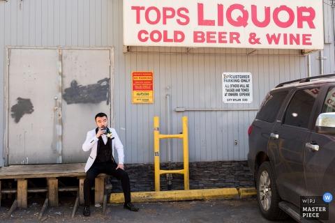 Der Hochzeitsfotograf aus Alberta hat dieses Porträt eines Bräutigams aufgenommen, der vor der Zeremonie außerhalb eines Spirituosenladens etwas trinkt