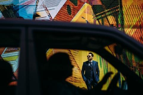 Un portrait très coloré du marié tourné à travers une fenêtre de voiture par le photographe de mariage Andreas Pollok d'Allemagne