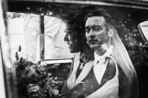France Wedding Reportage Le photographe Ronan Jégaden sait comment faire un portrait du marié avec sa nouvelle épouse, comme celui-ci en utilisant le verre réfléchi de la limousine.