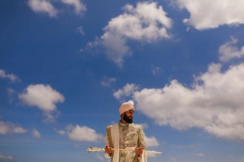 Rahul Khona de Londres est un photographe de mariage pour les mariages au Royaume-Uni où le marié est à l'aise en tenant une épée lors d'une séance de portrait.