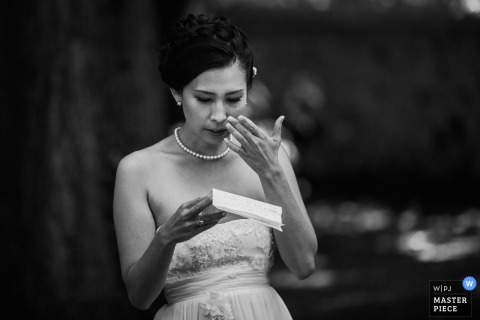 Lyon wedding photographer captured this black and white photo of a bride reading her speech from a piece of a paper as she wipes a tear from her cheek