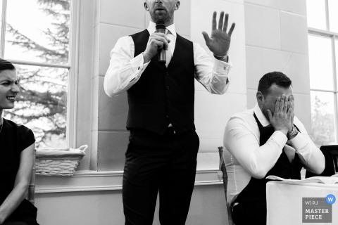 Nottinghamshire-Hochzeitsfotograf schuf dieses Schwarzweiss-Foto des Bräutigams, der sein Gesicht in der Demütigung bedeckt, während der Trauzeuge seine Rede hält