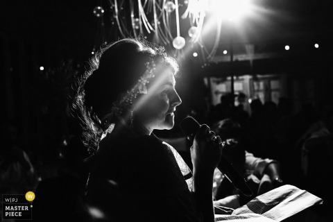 Lyon wedding photographer captured this silhouette photo of the bride wearing a floral headband giving a speech while the spotlight shines down on her