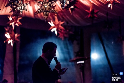 This silhouette photo of a groom giving his speech in a tent under a draped cloth ceiling and many paper stars was captured by a San Diego wedding photographer