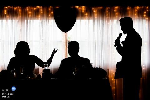 Die Silhouetten der Braut und des Bräutigams vor einem Vorhang aus funkelnden Lichtern wurden von einem Hochzeitsfotografen aus New Jersey aufgenommen