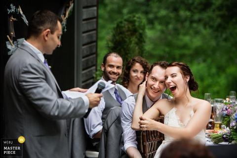 Der Hochzeitsfotograf aus New Jersey hat dieses Foto einer Braut aufgenommen, die ihren Bräutigam festhält, während sie bei ihrem Hochzeitsempfang im Freien Reden hörte