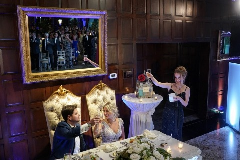 New York Wedding Photographer Emin Kuliyev creates interesting shots at wedding receptions, like this one of a toast with the guests reflected in a mirror on the wall.