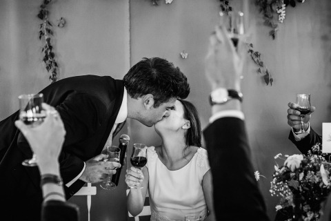 France Wedding Photographer William Lambelet created this black and white image of the bride and groom kissing while surrouded by toasting glasses.