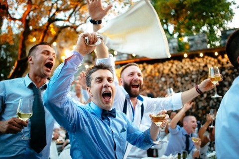 Wedding Photographer Alessandro Avenali of Roma, Italy captured the wedding guests drinking and having a good time in this color photograph.