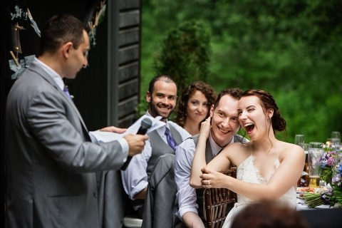 Wedding Photographer Todd Laffler of New Jersey captured the bride and groom laughing during outdoor reception speeches at this wedding.