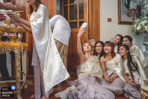 Fotograf ślubny z Bangkoku uchwycił druhny ubrane na biało, robiące selfie przed rozpoczęciem ceremonii