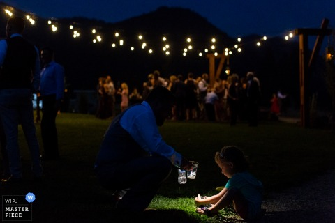This photo of a wedding guest using the flashlight on his phone to help a young child find something in the grass was captured by a Missoula wedding photographer