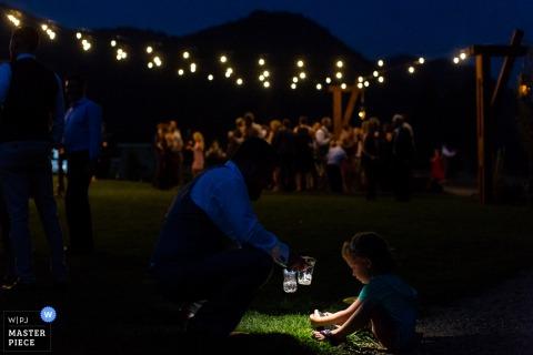 To zdjęcie gościa weselnego korzystającego z latarki na telefonie, aby pomóc małemu dziecku znaleźć coś na trawie, zostało zrobione przez fotografa ślubnego z Missoula