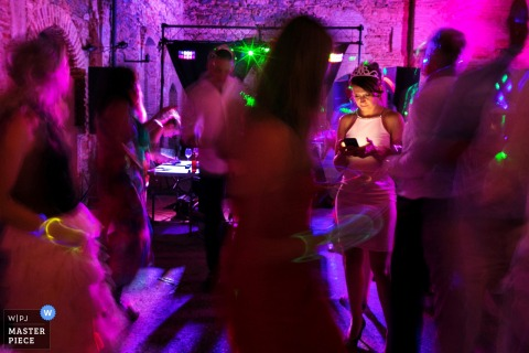 Through the blur of dancing bodies on the glowing pink dance floor, Madrid wedding photographer focuses on a guest who is texting on her phone