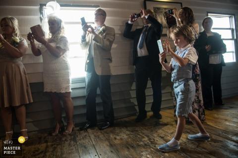Der Londoner Hochzeitsfotograf hat dieses Foto eines Kindes aufgenommen, das während des Hochzeitsempfangs einen Fotografen mit einem Mobiltelefon spielt, während eine Reihe von Erwachsenen dasselbe hinter ihm tut