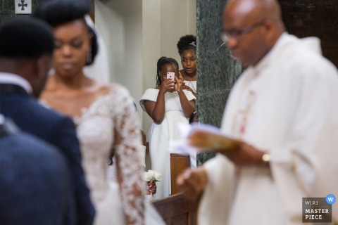 London wedding photographer caught a wedding a guest snapping a photo of the bride and groom saying their vows from a doorway off to the side