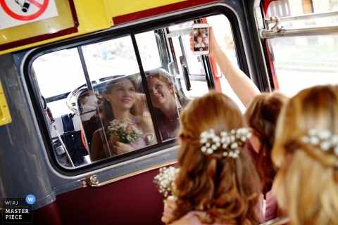 Hampshire wedding photographer uses a mirror to capture the bride and her mother taking a selfie on the bus