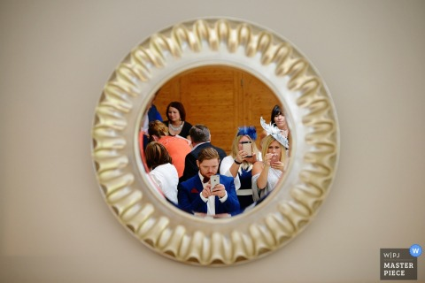 Hampshire wedding photographer uses a mirror to capture the wedding guests taking selfies as they wait for the reception to start