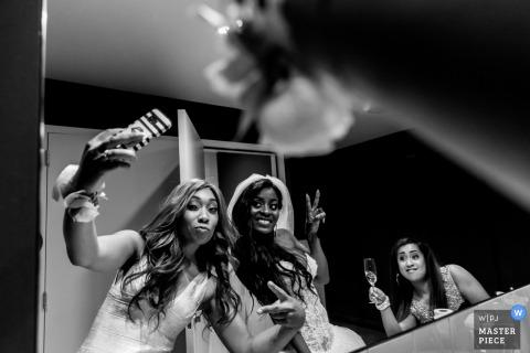 La photographe de mariage de Rotterdam a créé cette photo en noir et blanc en utilisant un miroir pour capturer le reflet de la mariée tandis qu'une demoiselle d'honneur prenait des selfies