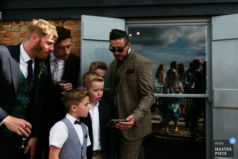 London wedding photographer captured this image of the groom sharing something on his cellphone while the groomsmen huddle close to watch
