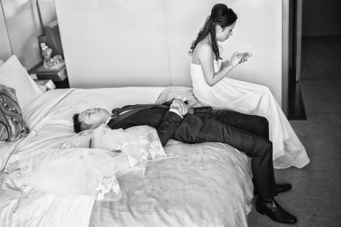 Wedding Photographer Fabio Mirulla of Arezzo, Italy recorded this bride and groom relaxing in the hotel room.