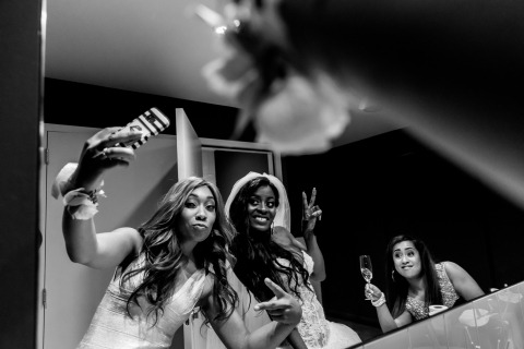 Netherlands Wedding Reportage Photographer Isabelle Hattink captured this image of the bride in the bathroom in a mirror with many phones.