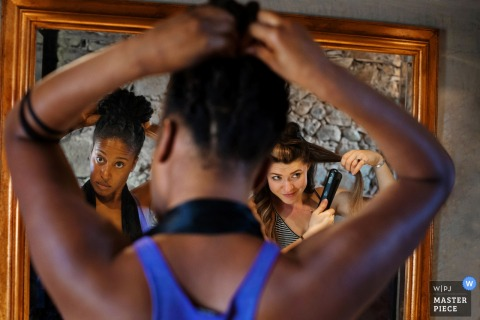 This photo of bridesmaids putting the finishing touches on their hair in the mirror was captured by a Madrid wedding photographer
