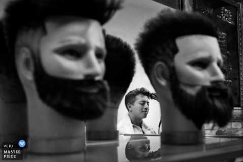 Madrid wedding photographer captured this photo of the groom getting his hair cut in the barbershop mirror while mannequins showcase beard trimming designs in the foreground