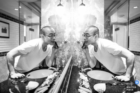London wedding photographer uses the bathroom mirror to create this black and white photo of a grooms pre-ceremony shave