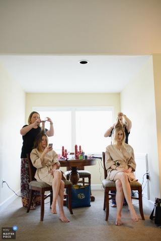 Deze foto van twee bruidsmeisjes die hun haar naast elkaar krijgen terwijl ze bijpassende gewaden dragen, is gemaakt door een trouwfotograaf van Outer Banks