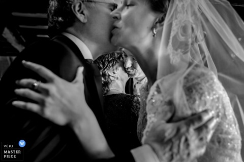 Overjissel wedding photographer captured this black and white photo of the bride and groom giving each other a sweet kiss on the cheek