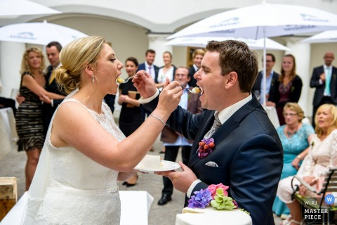 Munich wedding photographer captured this image of a bride and groom feeding each other cake at an outdoor reception